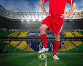 Composite image of football player standing with brasil ball — Stock Photo