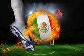 Football player kicking flaming mexico flag ball — Stock Photo