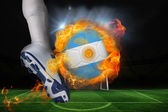 Football player kicking flaming argentina flag ball — Stock Photo