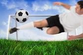 Football player in white kicking ball — Stock Photo