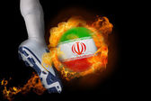 Football player kicking flaming iran ball — Stock Photo