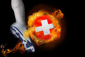 Football player kicking flaming switzerland ball — Stock Photo