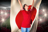 Composite image of cheering football fan in red holding japan fl — Stock Photo