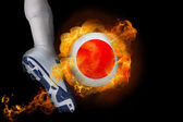 Football player kicking flaming japan ball — Stock Photo
