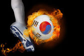 Football player kicking flaming korea republic ball — Stock Photo