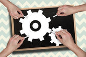Multiple hands drawing cogs with chalk — Stock Photo