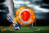 Football player kicking flaming japan flag ball — Stock Photo