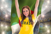 Pretty football fan in brasil t-shirt holding flag — Stock Photo