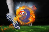 Football player kicking flaming australia flag ball — Stock Photo
