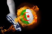 Football player kicking flaming algeria ball — Stock Photo