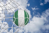 Composite image of football in nigeria colours at back of net — Stock Photo