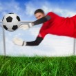 Fit goal keeper jumping up saving ball — Stock Photo #46750811