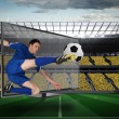 Composite image of football player in blue kicking ball out of t — Stockfoto #46754755