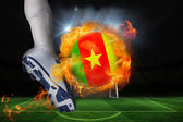 Football player kicking flaming cameroon flag ball — Stock Photo