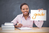 Happy teacher holding page showing grade — Stock Photo