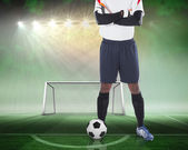 Composite image of goalkeeper standing with ball — Stock Photo