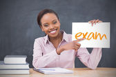 Happy teacher holding page showing exam — Stock Photo