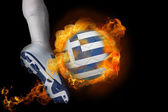 Football player kicking flaming greece flag ball — Stock Photo