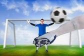 Football player striking ball at goalkeeper — Stock Photo