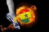 Football player kicking flaming ghana flag ball — Stock Photo