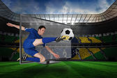 Composite image of football player kicking ball through tv — Stock Photo