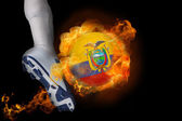 Football player kicking flaming ecuador ball — Stock Photo