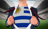 Businessman opening shirt to reveal uruguay flag — Stock Photo