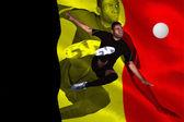Football player in black kicking — Stock Photo