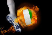 Football player kicking flaming ivory coast ball — Stock Photo