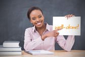 Happy teacher holding page showing well done — Stock Photo