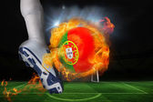 Football player kicking flaming portugal flag ball — Stock Photo