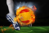 Football player kicking flaming spain flag ball — Stock Photo