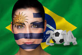Composite image of uruguay football fan in face paint — Stock Photo