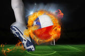Football player kicking flaming chile flag ball — Stock Photo
