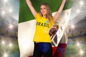 Excited football fan in brasil tshirt holding flag — ストック写真