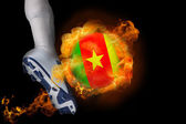 Football player kicking flaming cameroon ball — Stock Photo