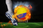 Football player kicking flaming colombia flag ball — Stock Photo