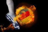 Football player kicking flaming germany ball — Stock Photo