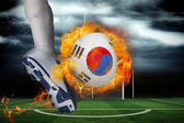 Football player kicking flaming south korea flag ball — Stock Photo