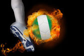 Football player kicking flaming nigeria ball — Stock Photo