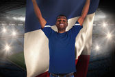 Composite image of cheering football fan in blue jersey holding  — Stock Photo