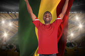 Excited handsome football fan cheering holding flag — Stock fotografie