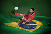 Composite image of football player in red kicking — Stock Photo