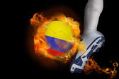 Football player kicking flaming colombia ball — Stock Photo