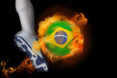 Football player kicking flaming brasil ball — Stock Photo