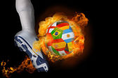 Football player kicking flaming international flag ball — Stock Photo