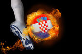 Football player kicking flaming croatia ball — Stock Photo
