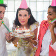 Businesswoman blowing out candles on cake — Stock Photo