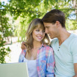 Couple on park bench using laptop — Stock Photo