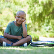 Happy schoolboy sitting on grass — Stock Photo #46788317